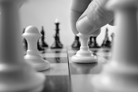 skillful: Low angle view between chess pieces of the fingers of a person making a move gripping a chess piece in a game of intelligence and skillful strategy planning