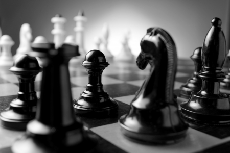 Close up low angle corner view of chess pieces lined up on a chess board ready for a game with focus to a black pawn with a castle and knight in the foreground photo