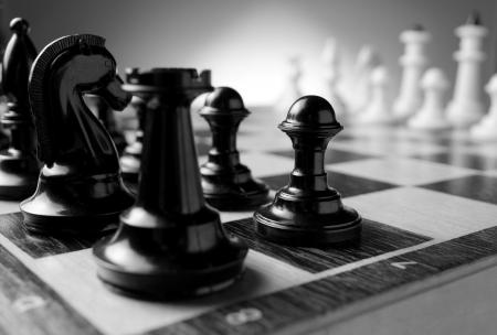 フォア グラウンドで騎士とお城と黒のポーンに焦点を当てたゲームの準備のチェス盤に並んでチェスの駒の低角コーナー ビューをクローズ アップ