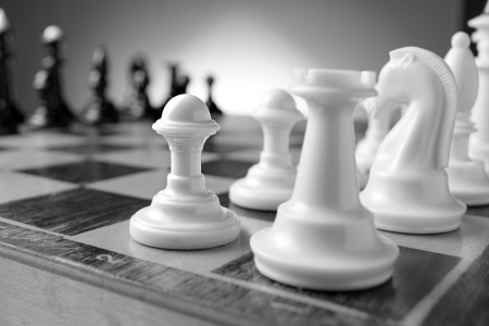 Game of chess with chess pieces lined up on their squares on either side of the board ready for a challenge with selective focus to one white pawn