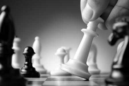 Conceptueel beeld beeltenis van het maken van een strategische zet met een hand verplaatsen van een schaakstuk op een schaakbord tijdens een behendigheidsspel
