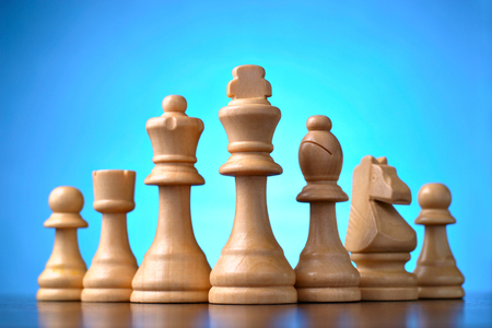 entertainment risk: Retro wooden chess pieces standing in a line on a reflective wooden surface against a blue background with central highlight