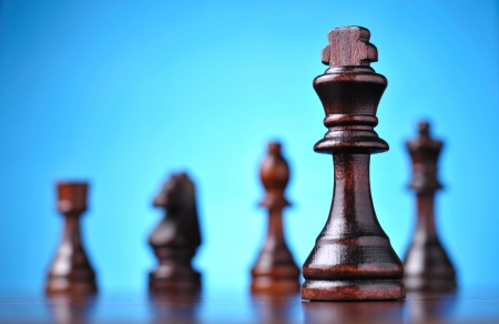 chess game: the figure of the black chess king in front of the other pieces of smaller advantage