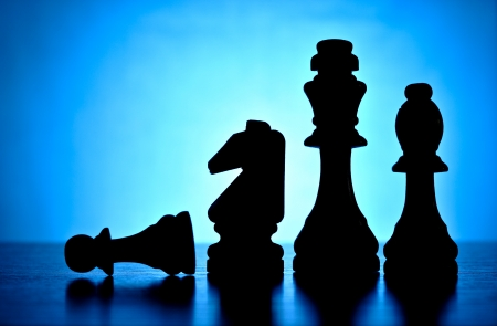 Silhouetted chess pieces against a backlit blue background with central highlight including a king, knight and bishop with a fallen pawn, copyspace for your text Reklamní fotografie