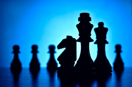 pices: Chess pices silhouetted against a blue background with a king flanked by a knight and queen in the foreground facing off against a row of pawns depciting strategy, skill and planning