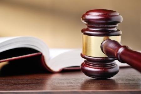 Richter aus Holz hämmern mit einer Messing-Band um den Holzhammer aufrecht stehend auf einem hölzernen Theke neben einem Buch Recht begrifflich von Urteilen und Strafverfolgung