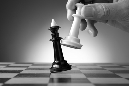 tactic: Conceptual image depicting making a strategic move with a hand moving a chess piece on a chessboard during a game of skill Stock Photo