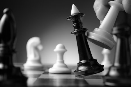 Conceptual image depicting making a strategic move with a hand moving a chess piece on a chessboard during a game of skill Stock Photo