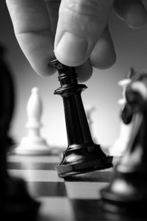 pensamiento estrategico: Imagen conceptual que representa hacer un movimiento estrat�gico con una mano que se mueve una pieza de ajedrez en un tablero de ajedrez en un juego de habilidad Foto de archivo