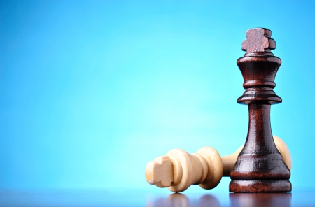 Two retro wooden chess pieces conceptual of Game Over with one black king standing upright alongside the defeated lighter chess piece against a graduated blue background with copyspace for your text photo