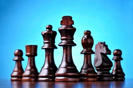 pensamiento estrategico: Piezas de ajedrez de madera retro de pie en una línea en una superficie de madera reflexivo sobre un fondo azul con relieve central Foto de archivo