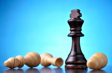 chess game: Winning in chess with a black wooden king standing upright over vanquished fallen pawns against a blue background with highlight and copyspace Stock Photo