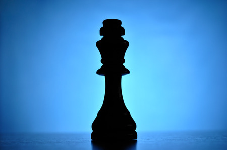 centred: Single King chess piece centred and silhouetted against a highlight on a blue background with copyspace on either side