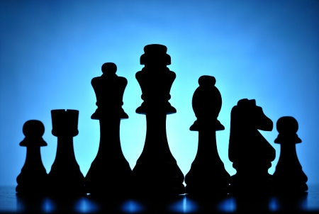 entertainment risk: Conceptual image of chess pieces in a row silhouetted and backlit against a graduated blue light with central highlight