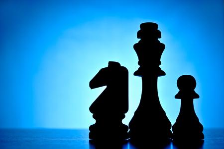 pensamiento estrategico: Tres piezas de ajedrez siluetas a contraluz sobre un fondo azul claro con un rey caballero y peón y copypsace para el texto