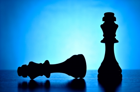 foe: The winner and the loser depicted by two chess pieces with the victorious king standing upright over his fallen competition or foe silhouetted against a graduated blue background with copyspace