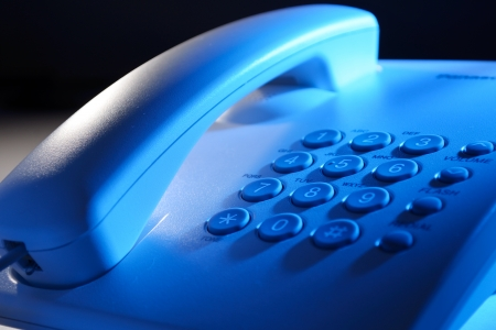 Close up view of the handset and keypad of a dial up telephone instrument with focus to the keys on the keypad in blue light photo