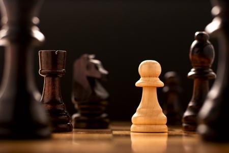 pensamiento estrategico: La perseverancia en la cara de un reto, una imagen conceptual de una luz peón de madera de color solitaria de pie en un tablero de ajedrez rodeado de todas las piezas de ajedrez negras, vista de ángulo bajo Foto de archivo
