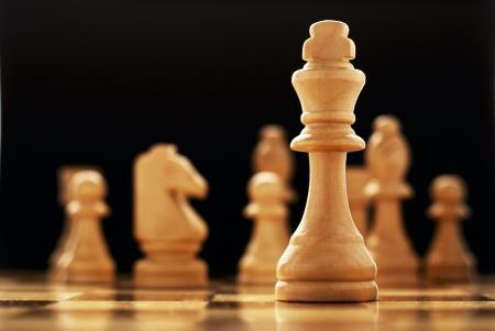pensamiento estrategico: El ganador - un rey pieza de ajedrez de madera de color claro - de pie solo en un tablero de ajedrez con el resto de las piezas visibles en la distancia detrás de él, el enfoque selectivo