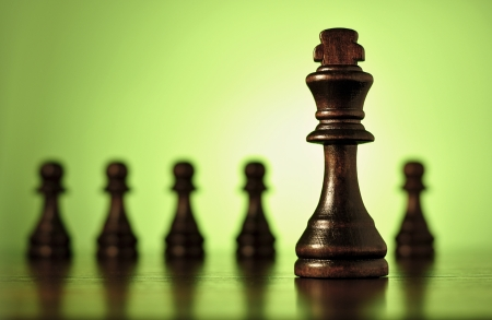 Conceptual image with a close up view of a wooden king chess piece with a row of blurred pawns in the background against green with copyspace Stock Photo