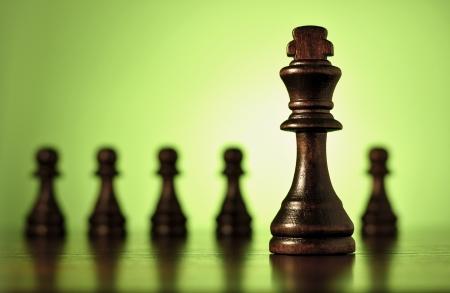pensamiento estrategico: Imagen conceptual con una vista de primer plano de una pieza de ajedrez rey de madera con una fila de peones borrosas en el fondo contra el verde con copyspace