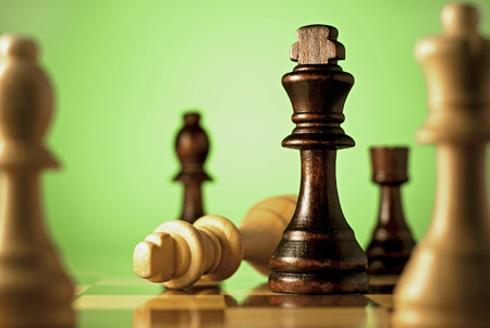 declaring: Chess, a game of skill and planning with the winning dark king chess piece declaring check mate on the fallen light wood king in a concept of winning and leadership