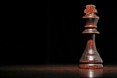 pawn to king: Low angle view of a dark wood king chess piece on a reflective wooden surface against a dark background with copyspace Stock Photo