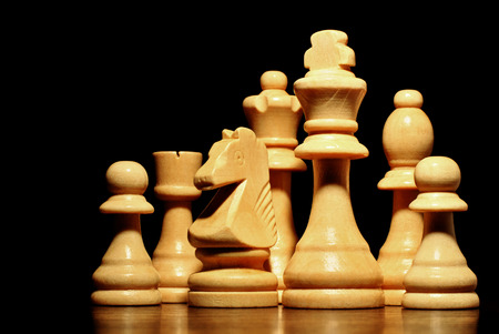 entertainment risk: Low angle view of a set of different chess pieces in a light coloured wood standing on a reflective wooden surface against a black background Stock Photo