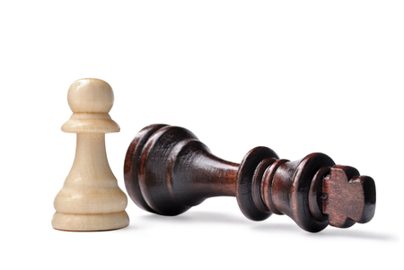 pawn king: Close up of two wooden chess pieces - king and pawn - on a white background with the pawn standing in a position of checkmate over the fallen king