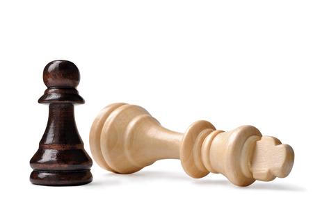 David et Goliath syndrome d'échecs avec un petit pion noir debout triomphant sur un roi de bois clair tombées sur un fond blanc