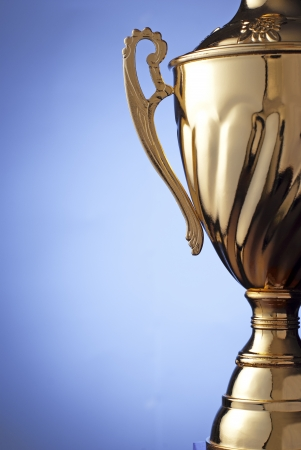 Close up of a silver metal trophy with a lid and handle to be presented to the winner of a competition, contest or championship on a blue background with copyspace
