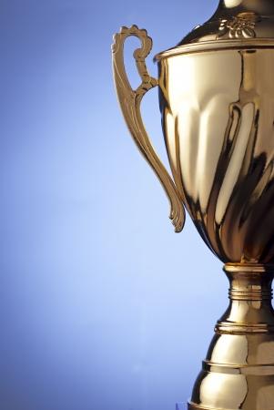 Nahaufnahme von einem silbernen Metall-Trophäe mit einem Deckel und Griff an die Gewinner eines Wettbewerbs, Wettbewerb oder Meisterschaft auf einem blauen Hintergrund mit Exemplar vorgelegt werden