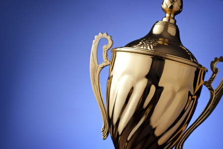 Close up of a silver trophy prize with an ornate lid and handles for the winner of a championship event or competition on blue with copyspace