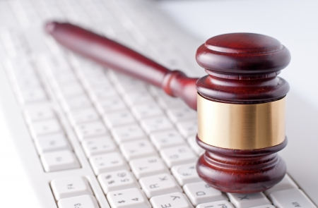 Conceptual image of a gavel used by a judge or auctioneer with a brass band around the head lying on a computer keyboard Stock Photo - 23796422