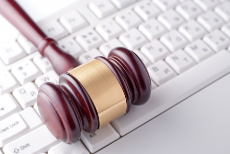 Conceptual image of a gavel used by a judge or auctioneer with a brass band around the head lying on a computer keyboard Stock Photo - 23796423