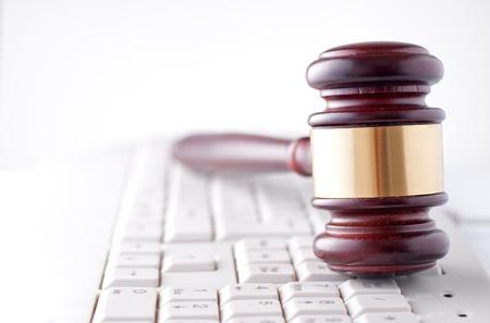 Image conceptuelle d'un marteau utilisé par un juge ou un commissaire-priseur avec un band autour de la tête couchée sur un clavier d'ordinateur