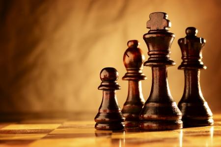 pensamiento estrategico: Pedazos de ajedrez de madera en pie en una línea en un tablero de ajedrez en la iluminación en tonos sepia dramática con copyspace