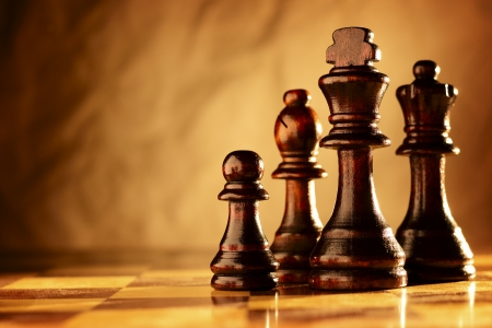 Pièces d'échecs en bois debout dans une ligne sur un échiquier dans l'éclairage aux tons sépia dramatique avec copyspace Banque d'images - 23830724