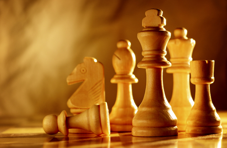 chess game: Chess pieces in light wood grouped together on a chessboard, low angle view with sepia toned lighting and copyspace