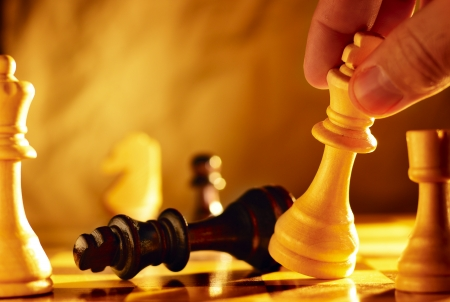 Close up view of the hand of a man going for checkmate in a game of chess using his king to knock over the opposing piece with dramatic sepia toned lighting and copyspace