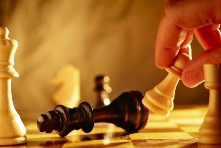 pensamiento estrategico: Hombre que hace un movimiento en una partida de ajedrez derribando una pieza de ajedrez con un pe�n que �l est� sosteniendo en su mano, vista de cerca del tablero de ajedrez