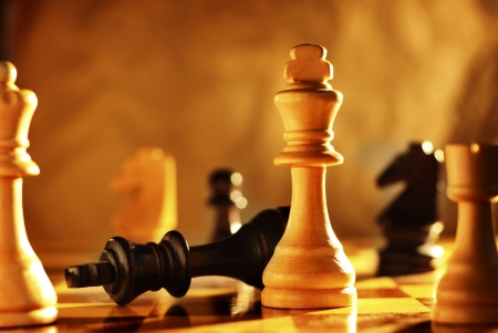 defeat: Winner and loser in a game of chess with focus to the two kings on the chessboard with one upended and one standing upright in a conceptual image