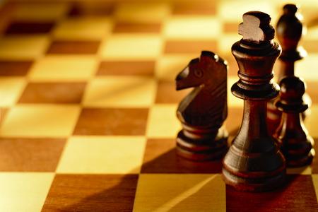 pensamiento estrategico: Piezas de ajedrez de madera oscura de pie sobre un tablero de ajedrez en un haz de ángulo bajo de la luz con el foco al rey y una gran área para la copia Foto de archivo