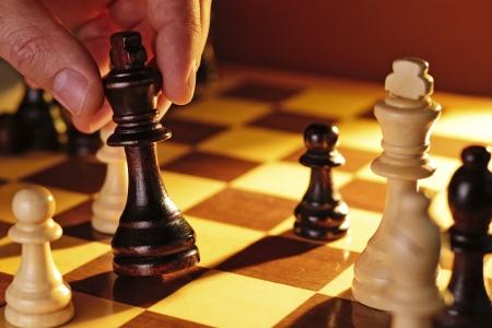 jugando ajedrez: Cierre de vista de la mano de un hombre de juego de ajedrez de hacer un movimiento que sostiene que el rey negro en la mano