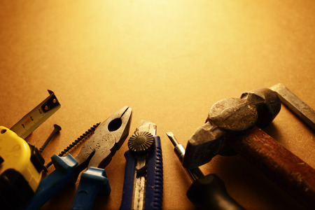 building maintenance: Sepia toned image of a toolkit for home maintenance with a screwdriver, hammer, pliers, knife, tape measure and nails arranged in a semi circle with copyspace Stock Photo