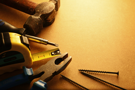building maintenance: Home maintenance tool kit in a sepia toned image arranged in a semi circle on the border with a hammer, pliers, screwdriver, tape measure and nails surrounding copyspace