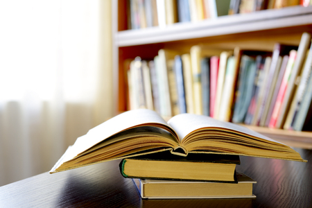 reference book: Close-up of an open book on a pile of old books, on a wooden table, with bookshelves in the background, as an invitation to study literature