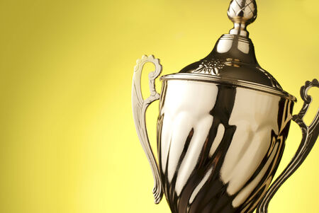 excellence: Close up of a silver metal trophy with a lid and handle to be presented to the winner of a competition, contest or championship on a yellow with copyspace Stock Photo