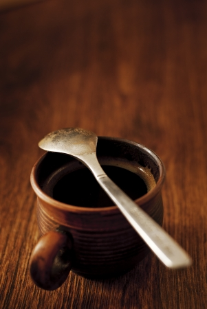 Cup of freshly brewed hot espresso coffee in a brown pottery mug served on a wooden table with a spoon for a refreshing morning stimulant photo
