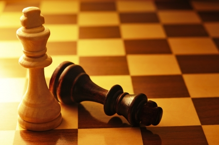 chessboard: Two King chess pieces on a chessboard with the dark king lying on its side at the foot of the victorious light wood King, conceptual image with copyspace